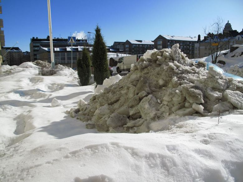 Bright sunny day and snow piles in Helsinki